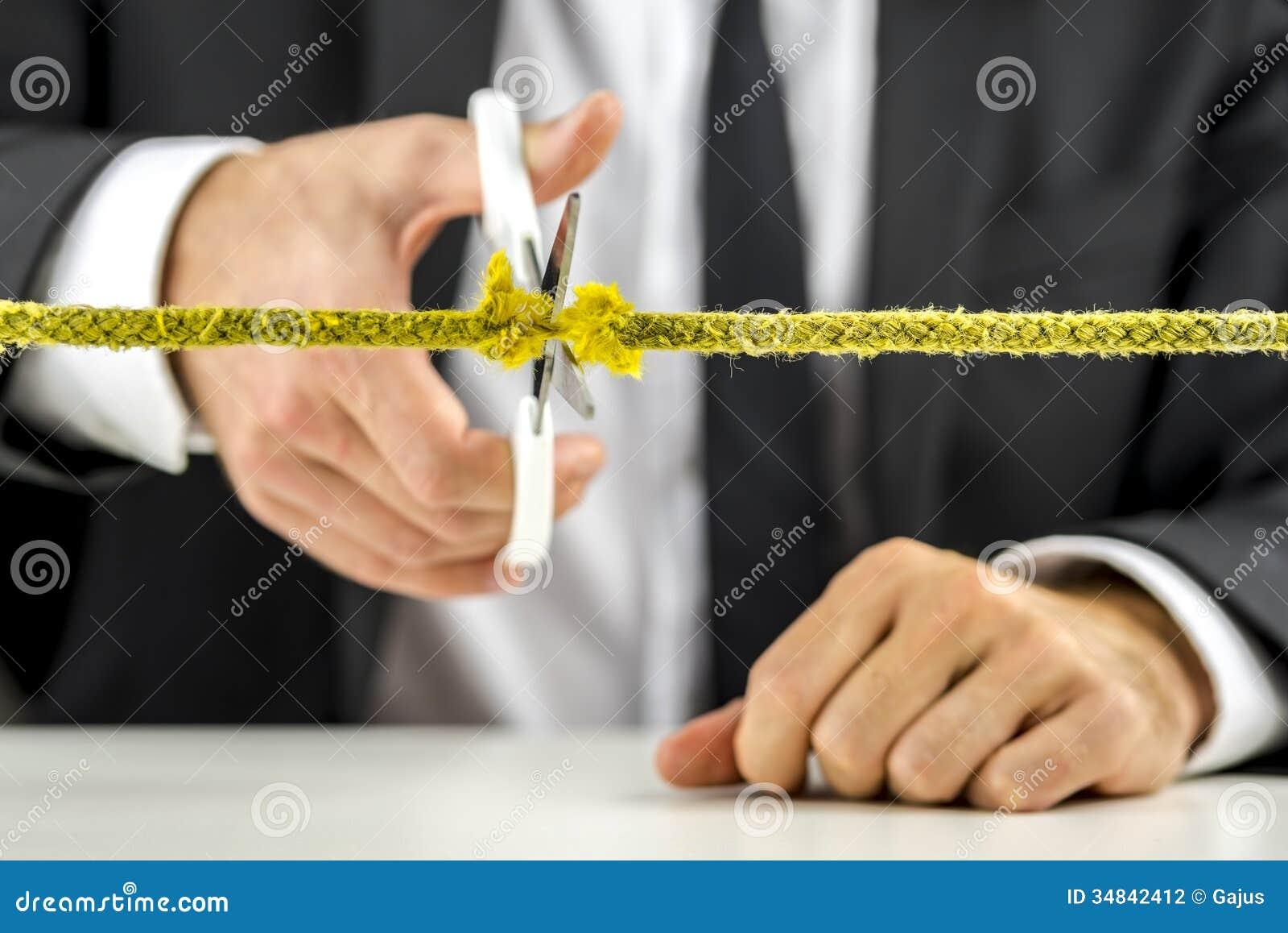 Businessman cutting yellow rope