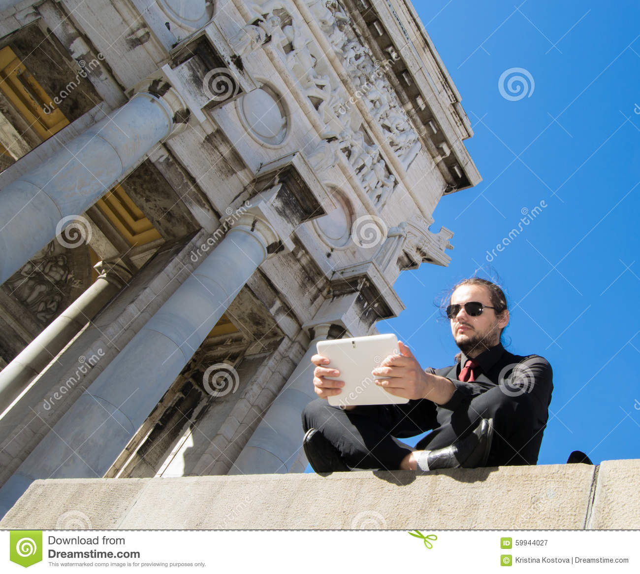 Businessman with dark suit and tablet - beautiful decorated architectonic background