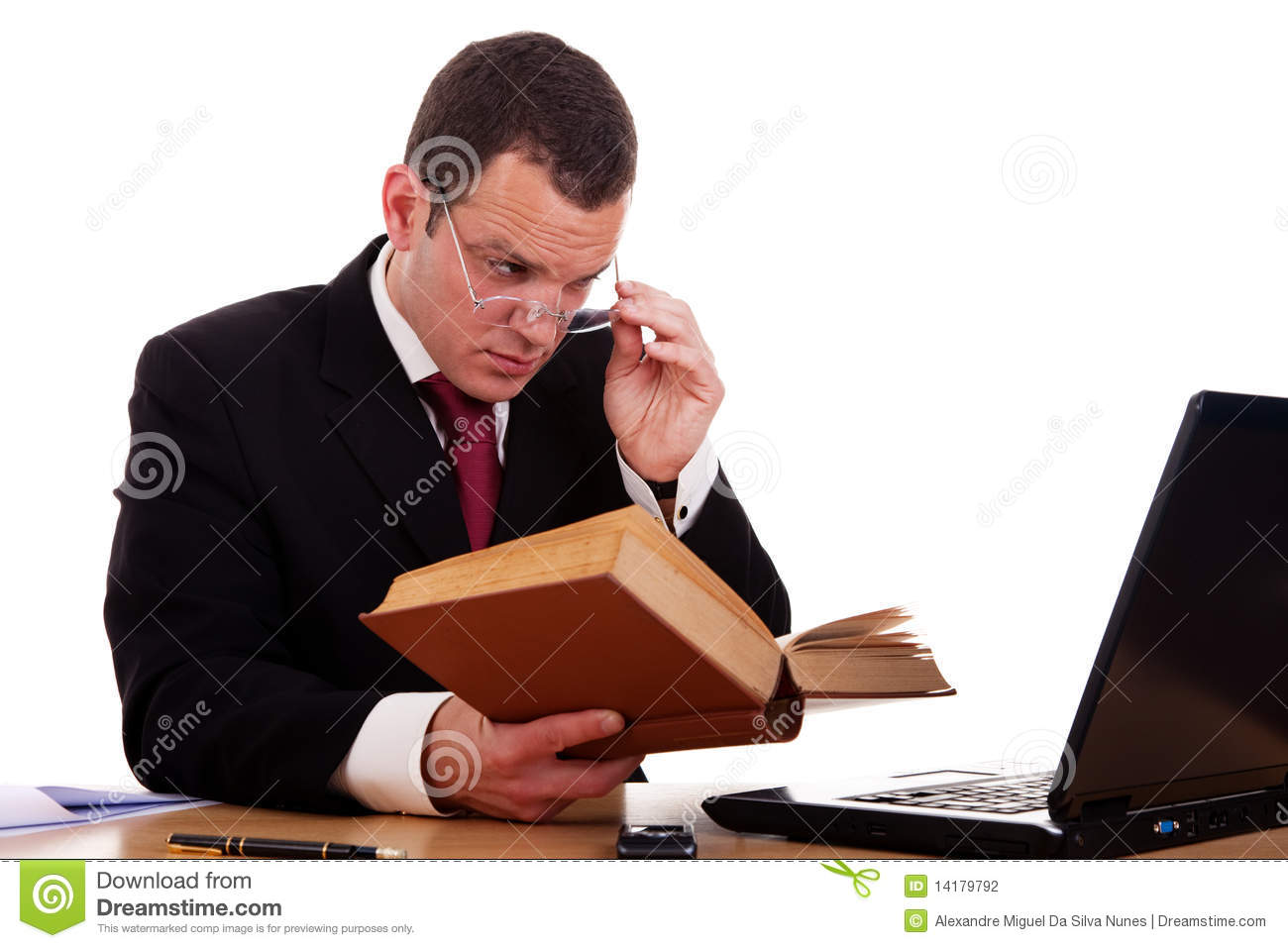 Businessman On Desk Reading And Studying Stock Photo