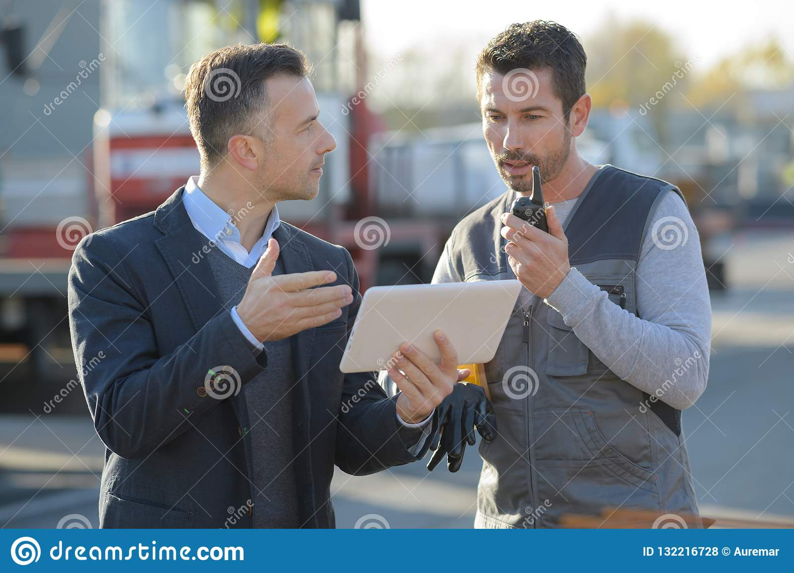 Businessman with digital tablet talking to worker outdoors