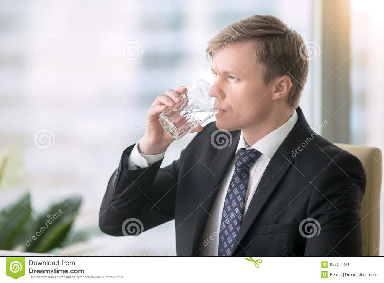 Businessman drinking water at the desk