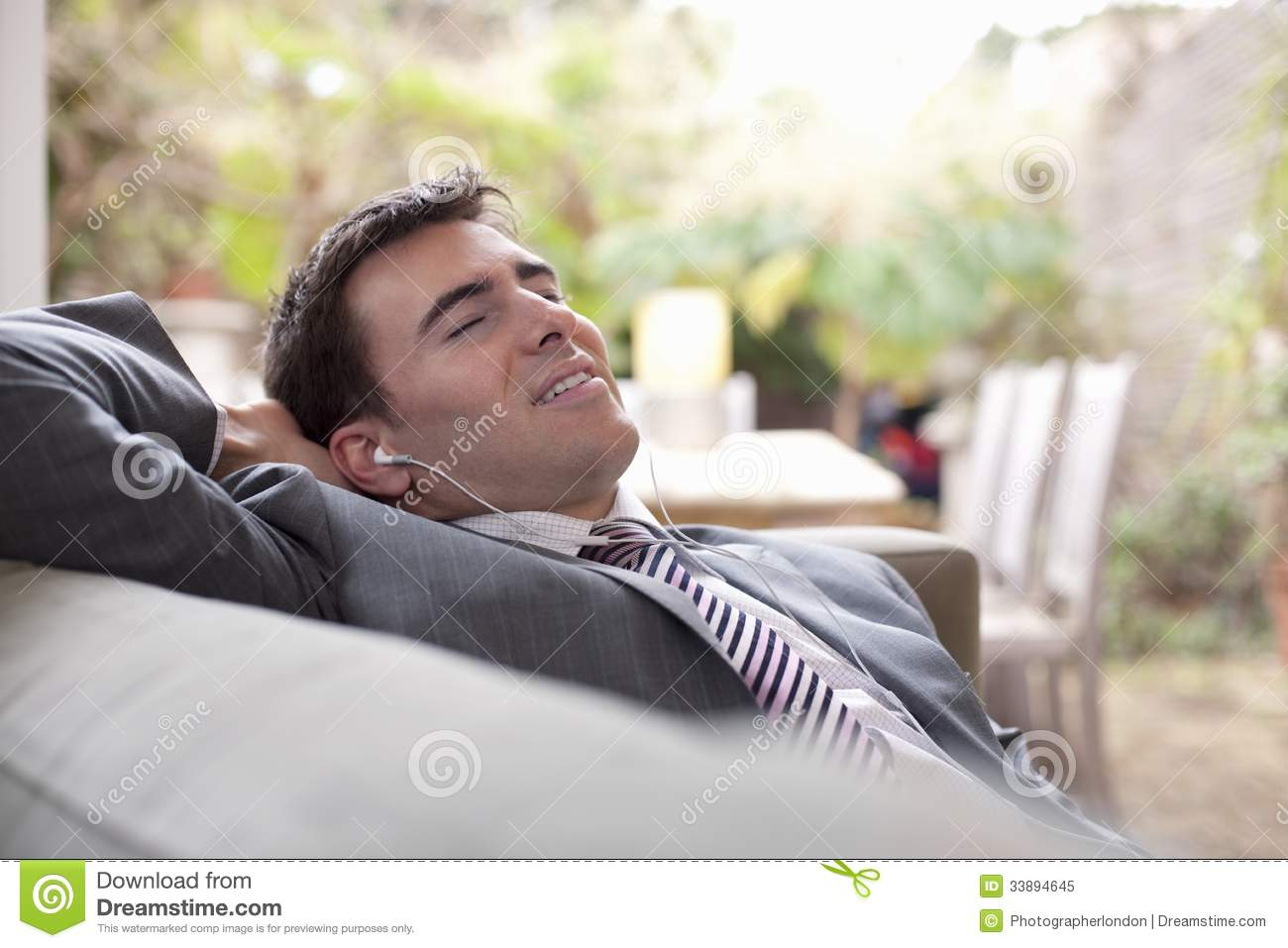 businessman with earphones relaxing at home royalty free. Black Bedroom Furniture Sets. Home Design Ideas