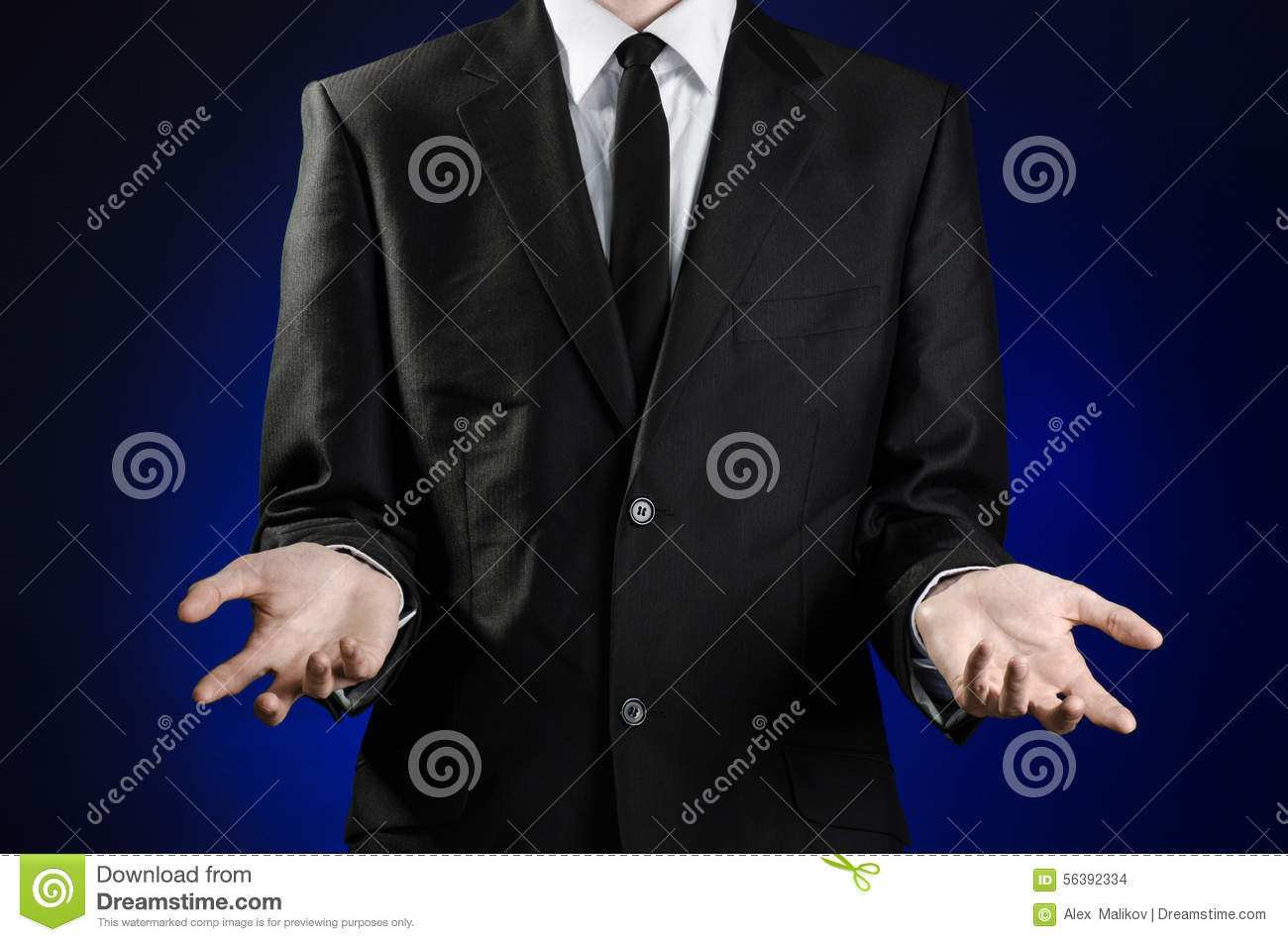 Businessman and gesture topic: a man in a black suit and white shirt showing gestures with hands on a dark blue background in stud