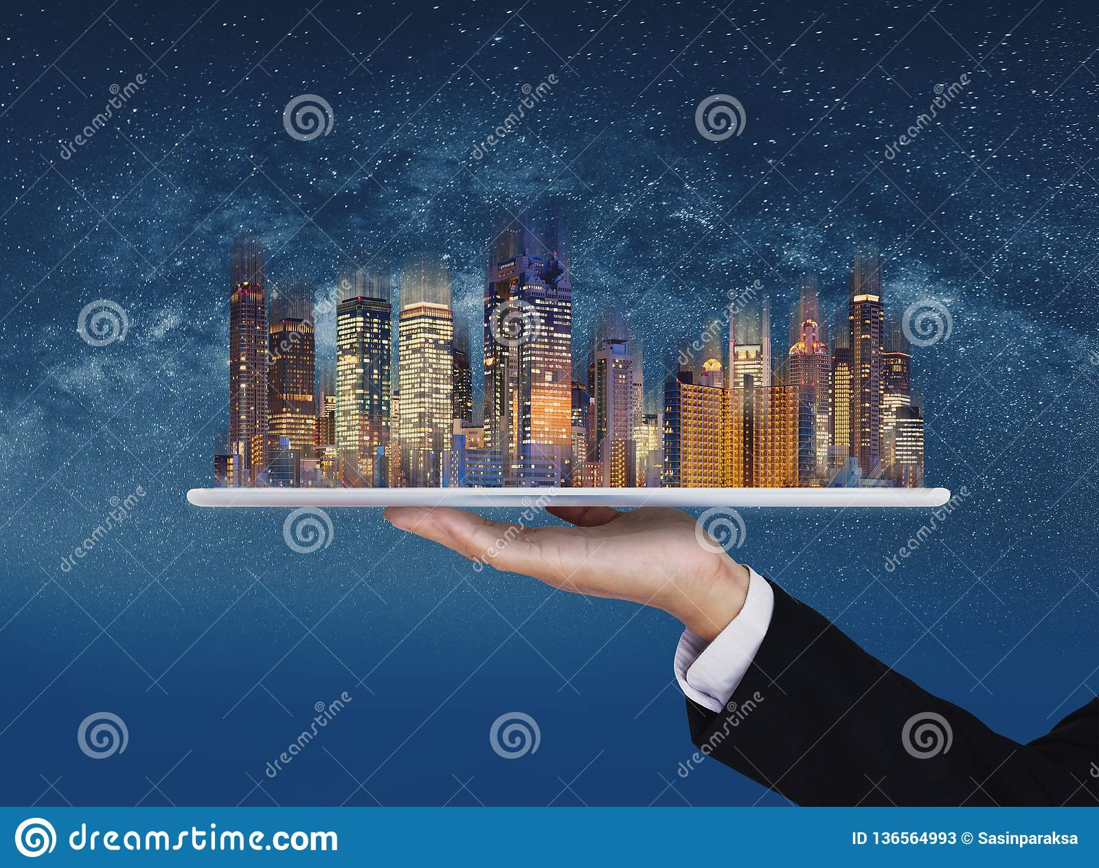 Businessman hand holding digital tablet with modern buildings hologram. Smart city, building technology and real estate business