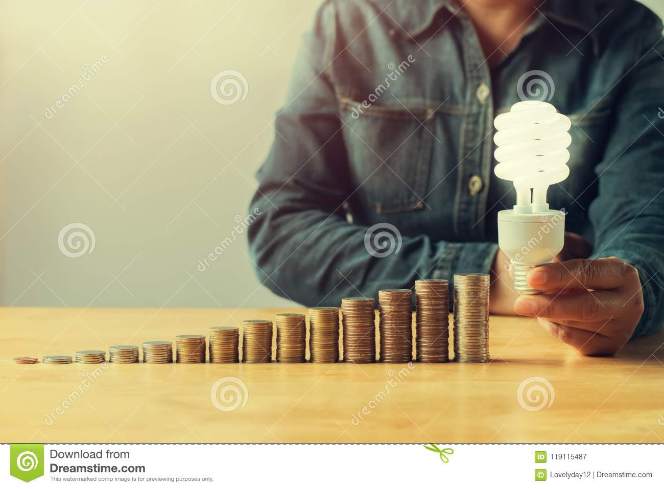 businessman hand holding led light and money stack on table in o