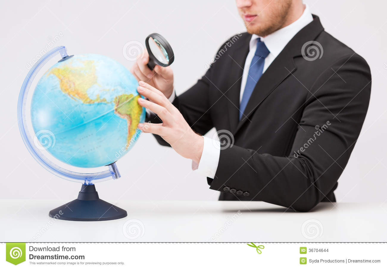 Technology Management Image: Businessman Hand Holding Magnifier Over Globe Stock Photo