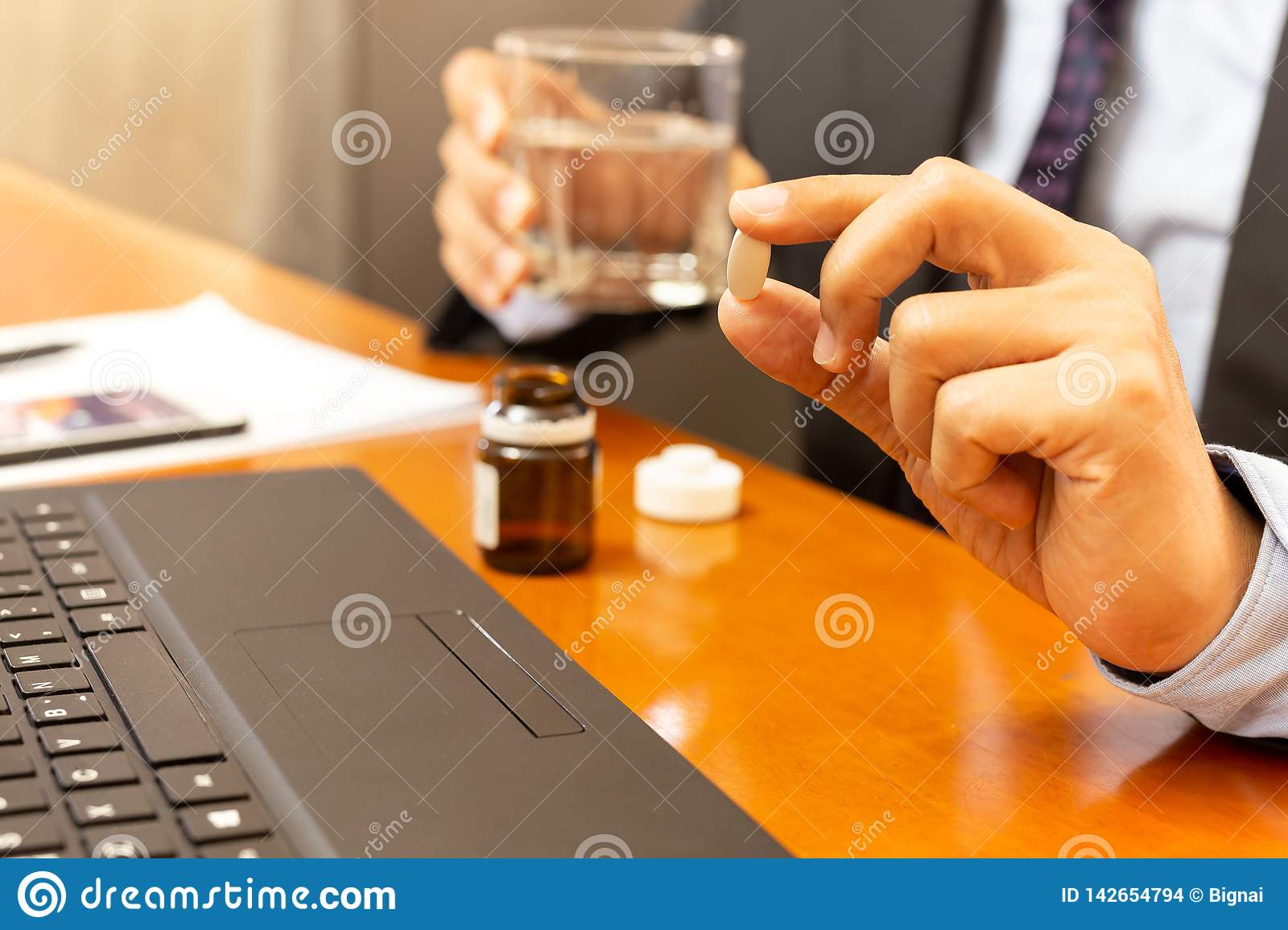 Businessman hand holding pill work with laptop health care concept.