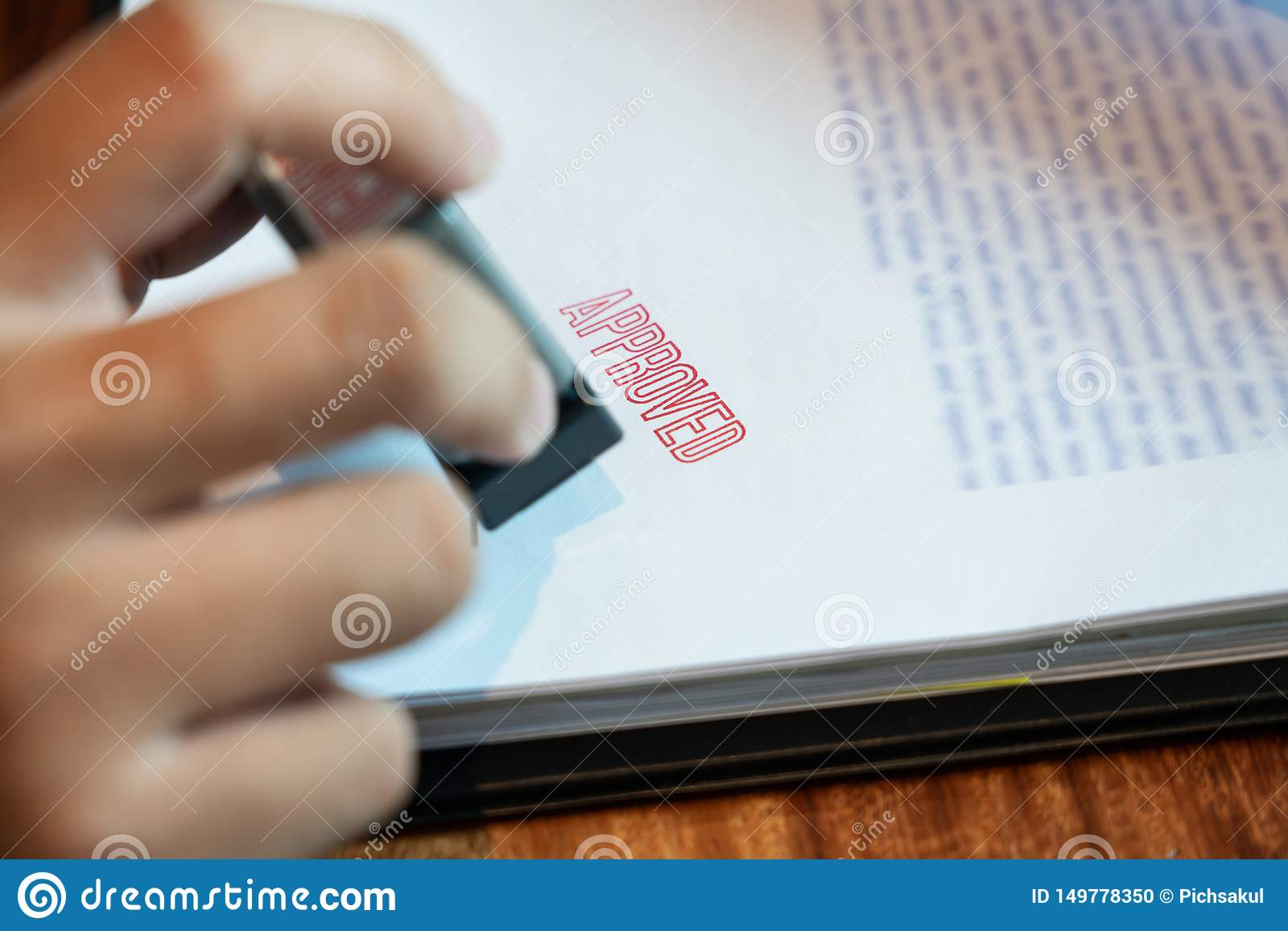 Businessman Hand notary public hand ink appoval stamper Stamping seal On Approved Contract Form documents contract, loan money
