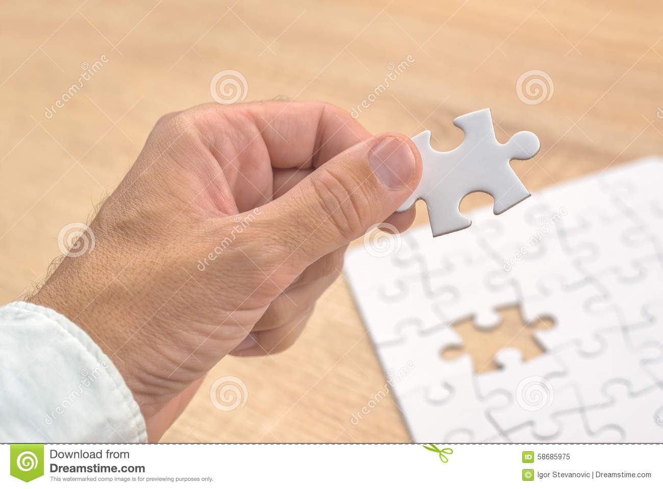 businessman hand putting a missing piece into jigsaw puzzle stock