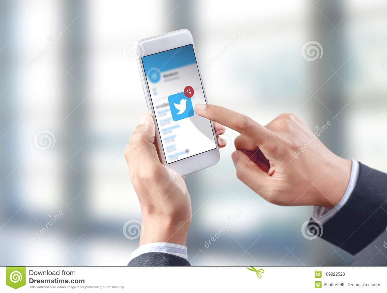 Businessman hand touch twitter icon on mobile screen
