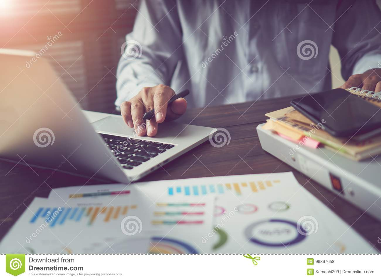Businessman hand working laptop on wooden desk in office in morning light. The concept of modern work with advanced technology.