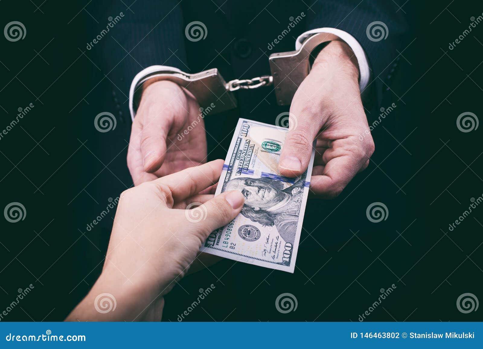 Businessman in handcuffs giving bribe