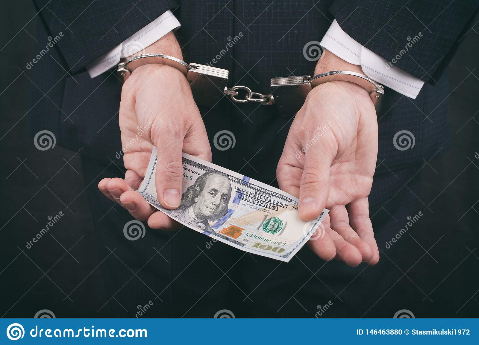 Businessman in handcuffs holding bribe hundred dollars