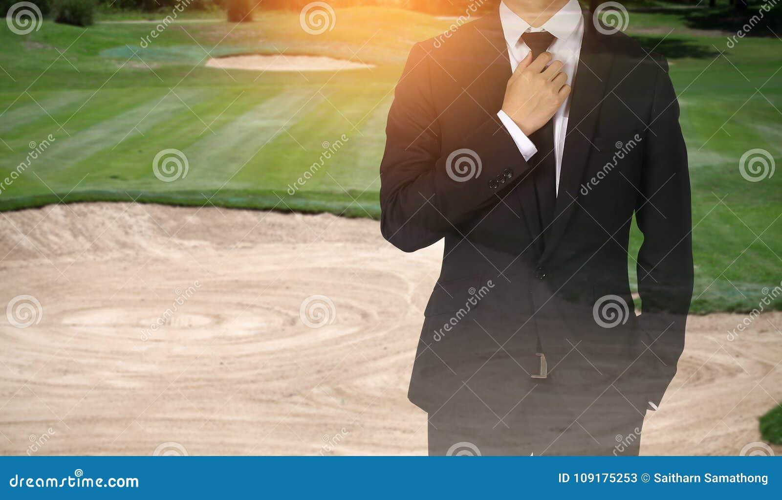 Businessman handles necktie showing confidence in golf course.