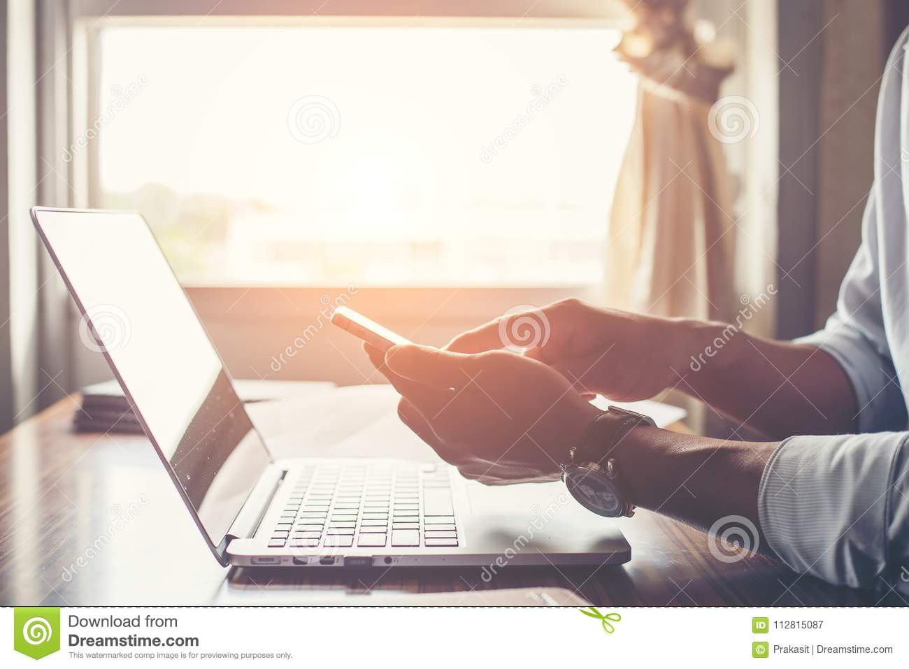 Businessman hands using cell phone with laptop at office desk.