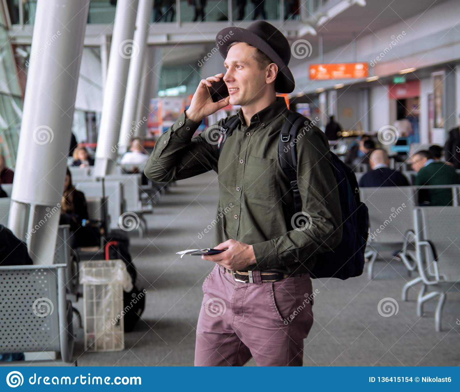 Businessman in a hat standing at the airport,talking by cellphone .
