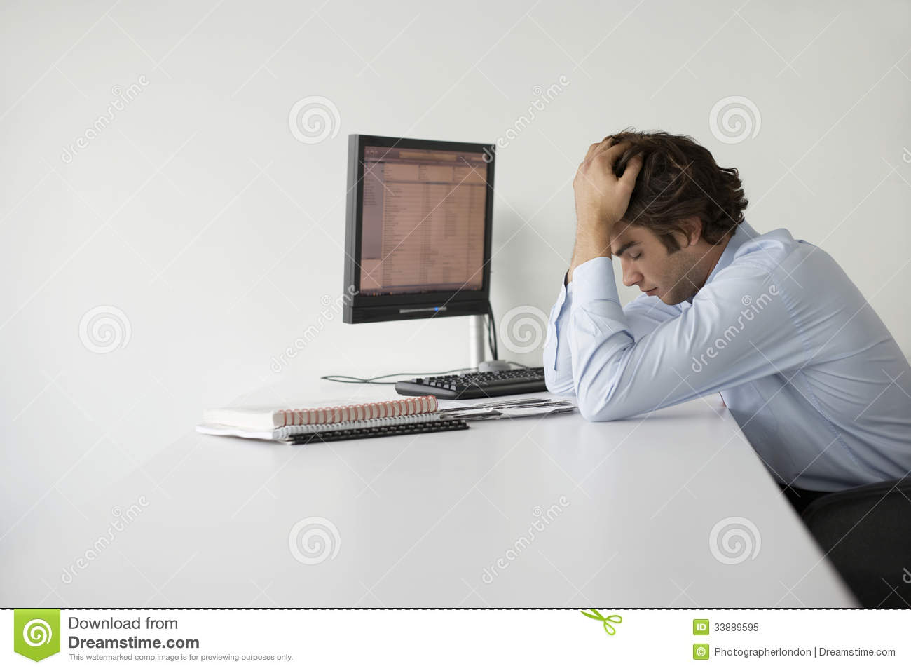 Businessman With Head In Hands At Office Desk Royalty Free Stock Photo