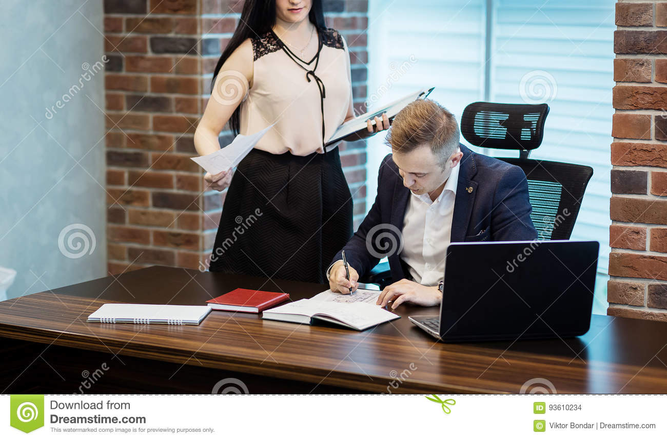 Businessman and his assistant Secretary in his office. The Secre