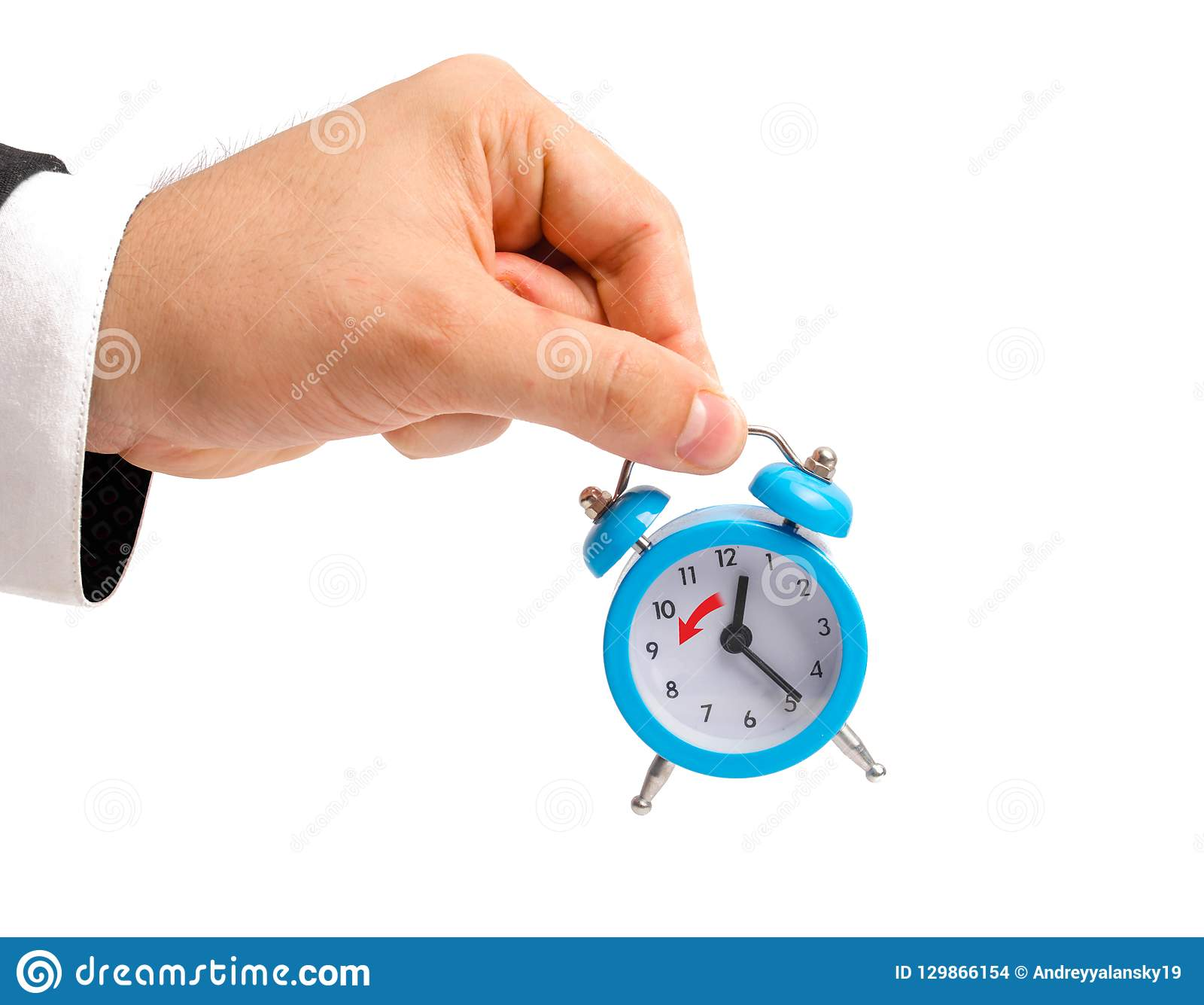 A businessman is holding an alarm clock. Transition to winter time, transfer of hours to an hour back. Watch in hand. The concept