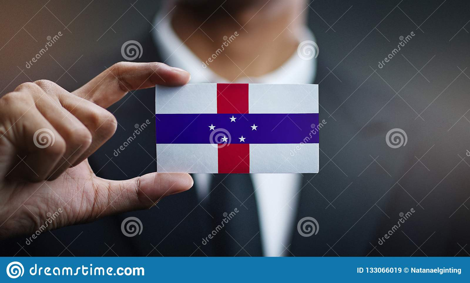 Businessman Holding Card of Netherlands Antilles Flag