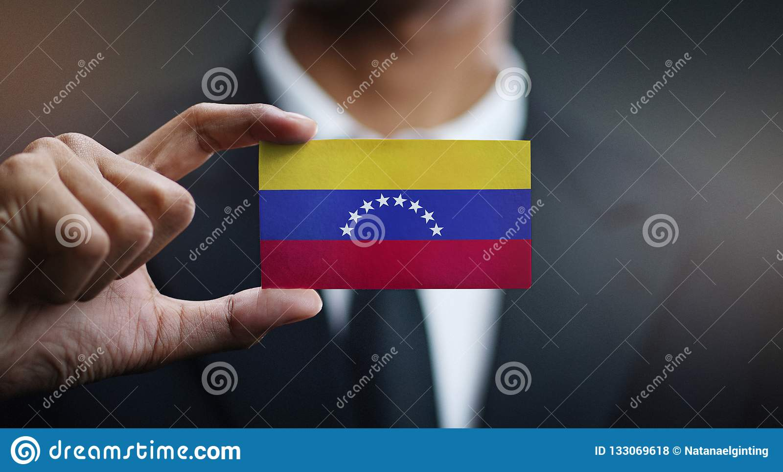 Businessman Holding Card of Venezuela Flag