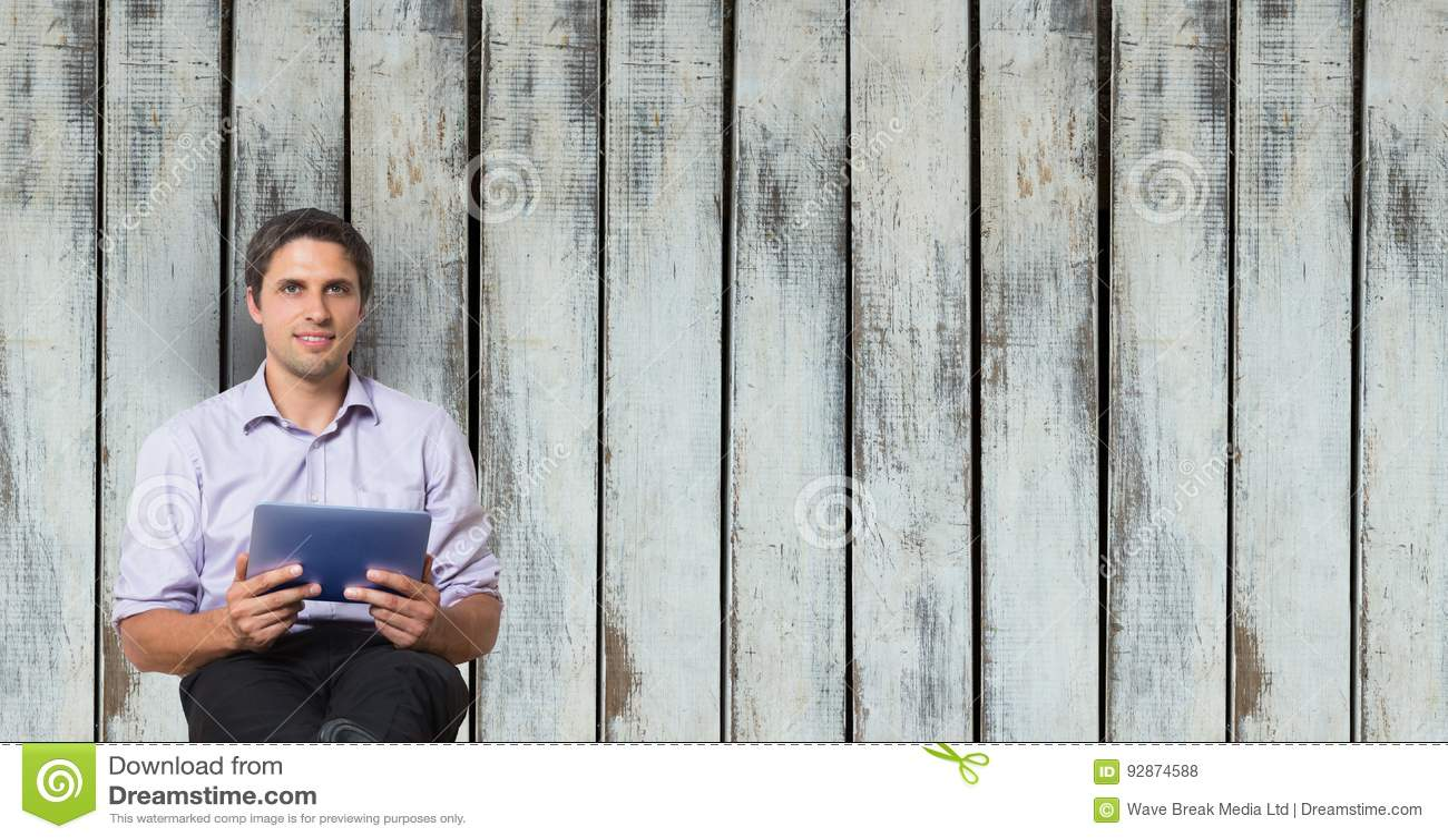 Businessman holding digital tablet against wooden wall