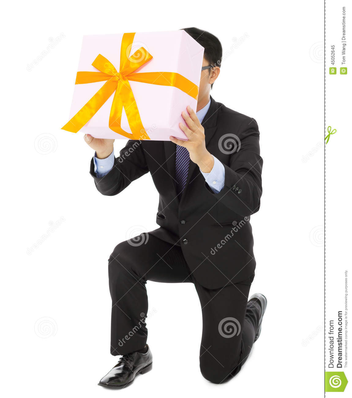 Businessman holding a gift box and kneel.
