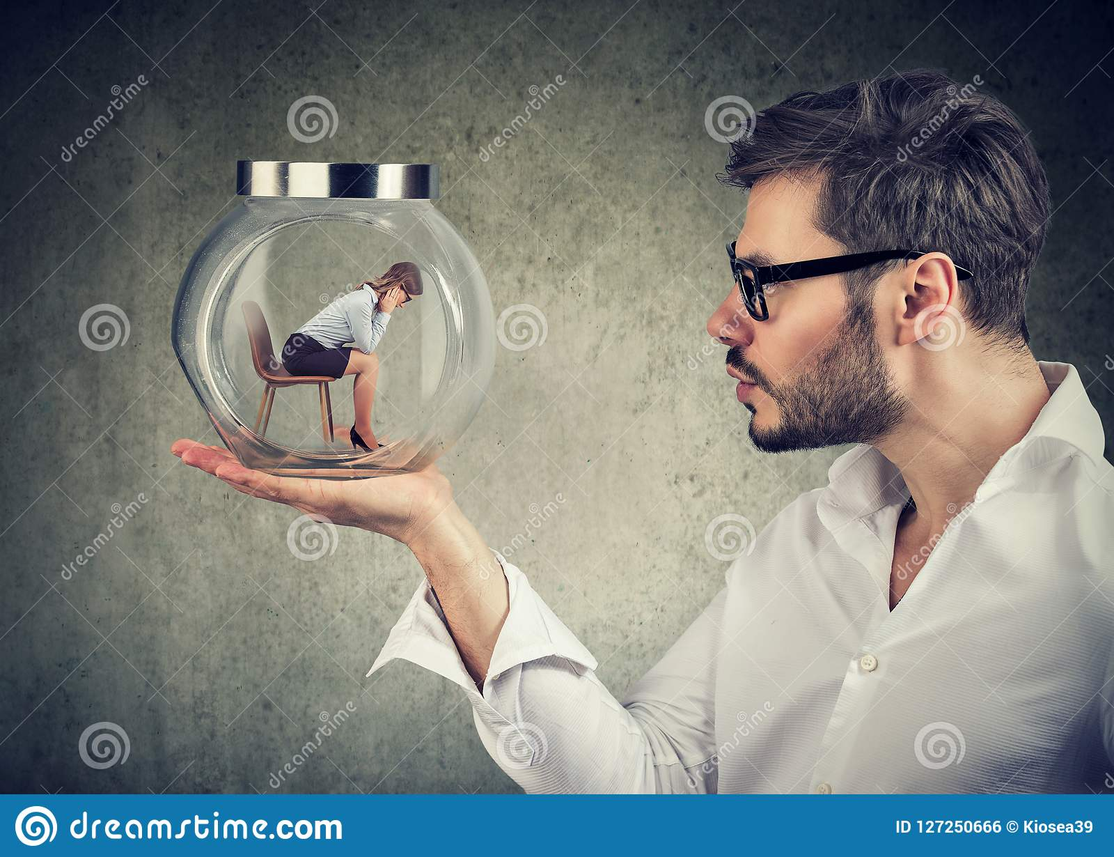Business man holding a glass jar with a young sad business woman trapped in it
