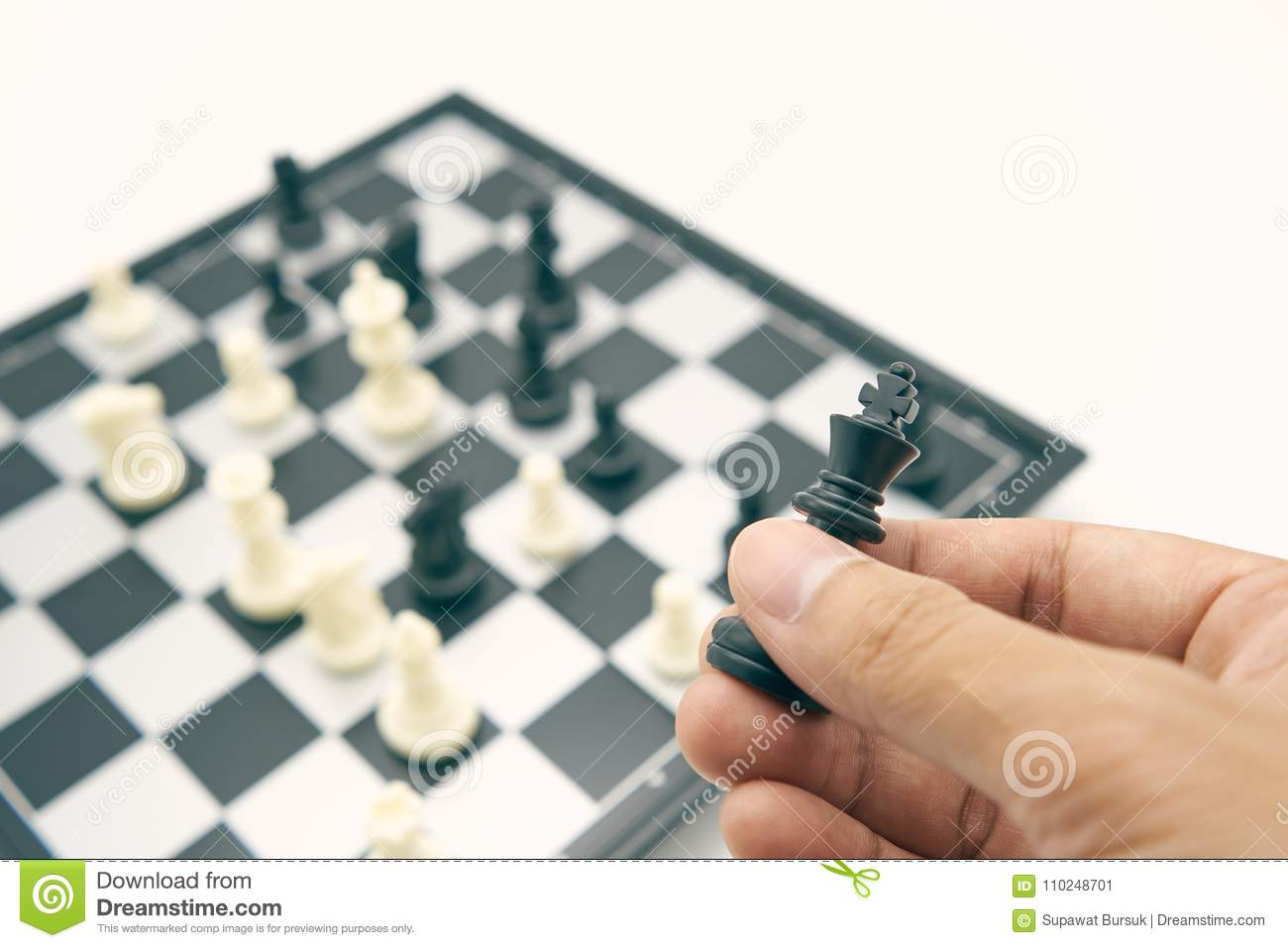 Businessman holding a King Chess is placed on Chess board.using as background business concept and Strategy concept with copy spac