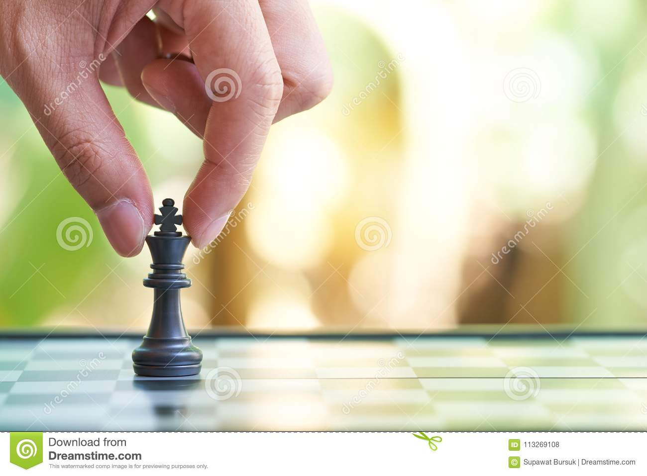 Businessman holding a King Chess is placed on a chessboard. using as background business concept and Strategy concept with copy sp