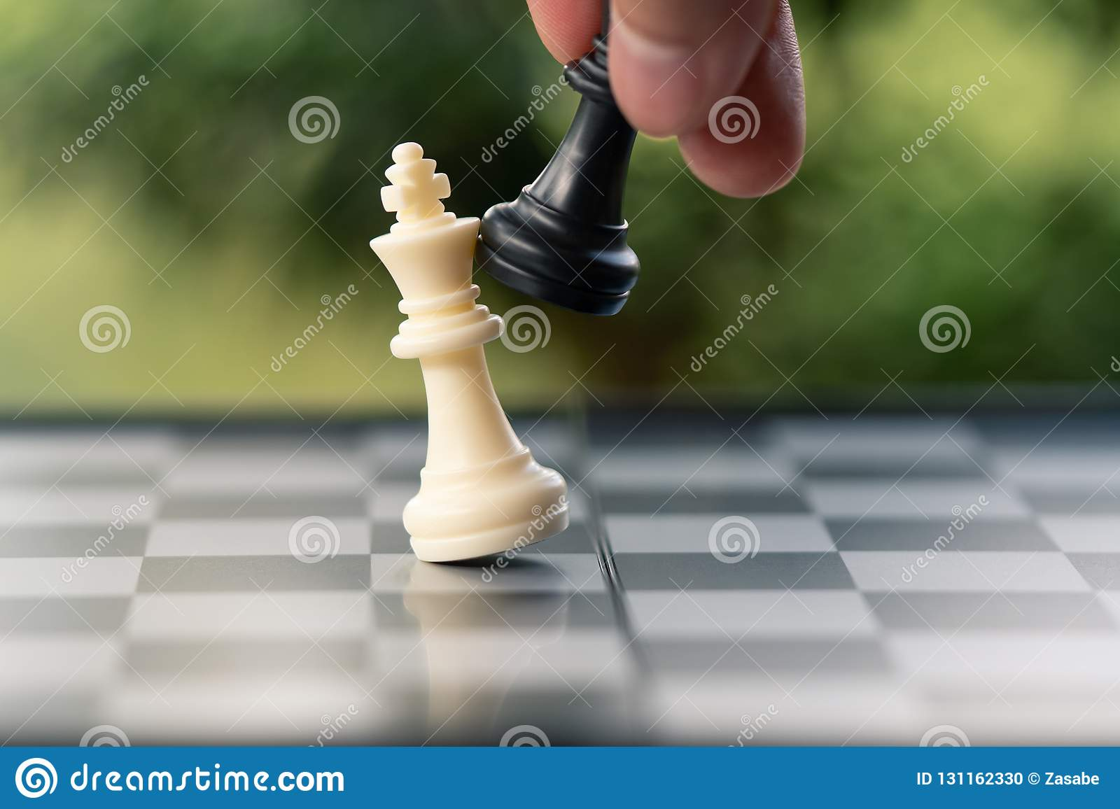 Businessman holding a King Chess is placed on a chessboard.using as background business concept and Strategy concept with copy sp