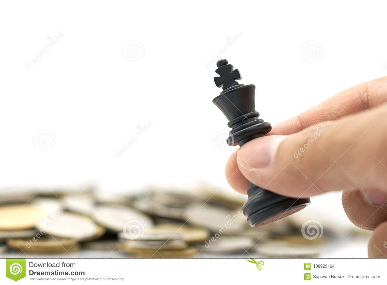 Businessman holding a King Chess is placed on a pile of coins. using as background business concept and Strategy concept