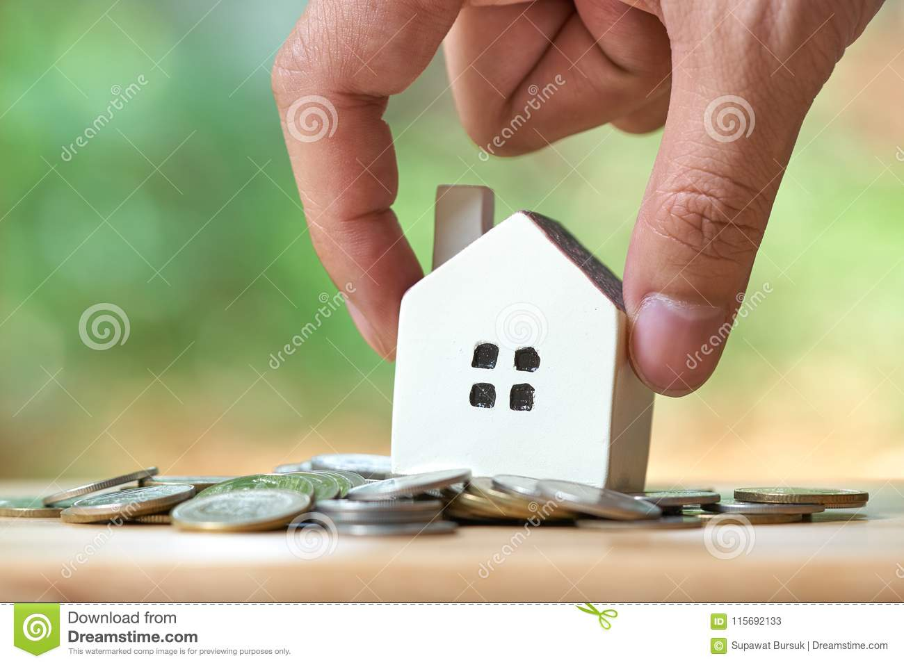 Businessman holding a model house model is placed on a pile of coins.using as background business concept and real estate concept