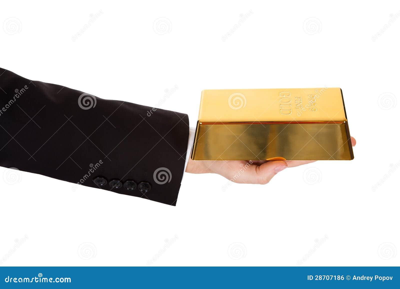 Businessman holding out a gold bar