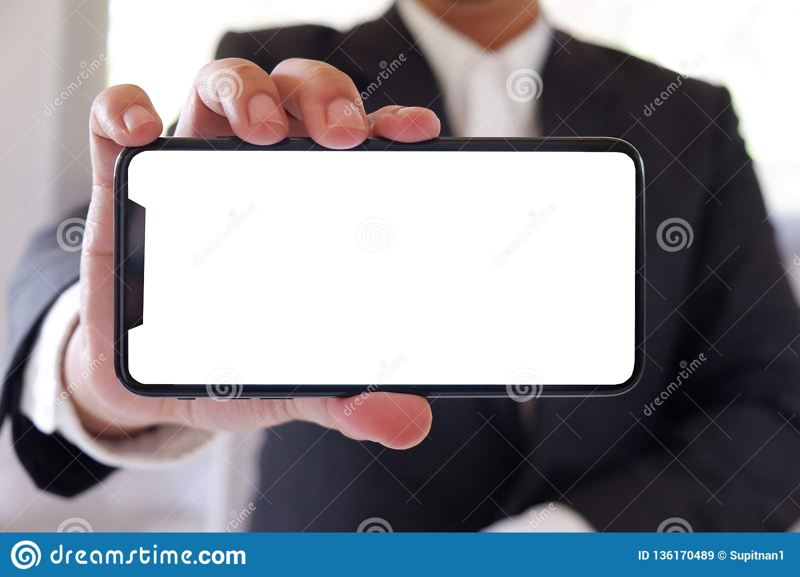 Businessman holding smartphone forward empty white screen for your text or picture.