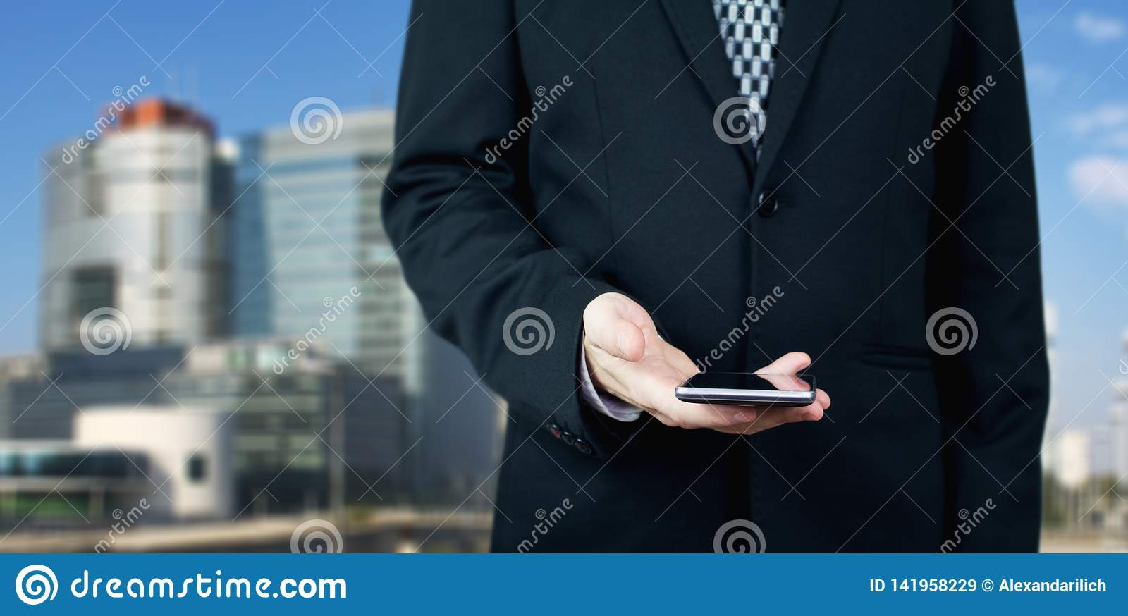Businessman Holding Smartphone in Hand With Business City and Corporate Buildings In Background