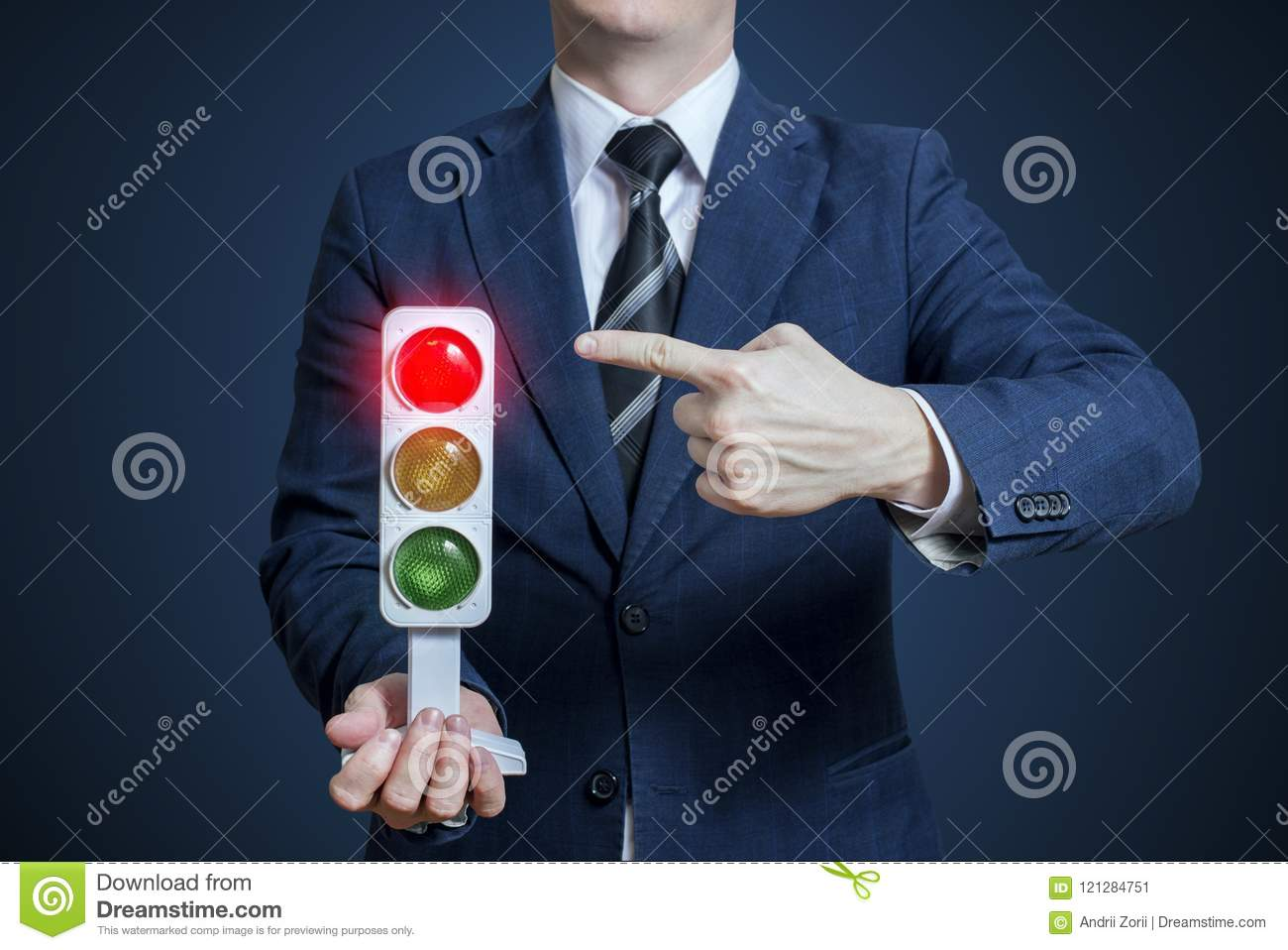Businessman holding a traffic light with red light on.