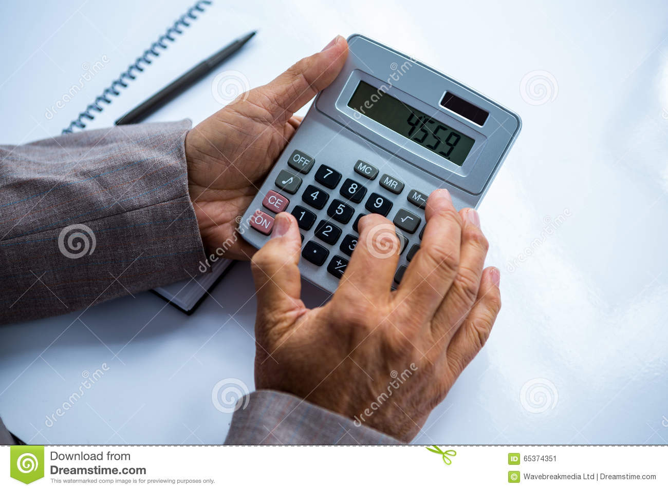 Businessman Holding And Using Calculator Stock Photo