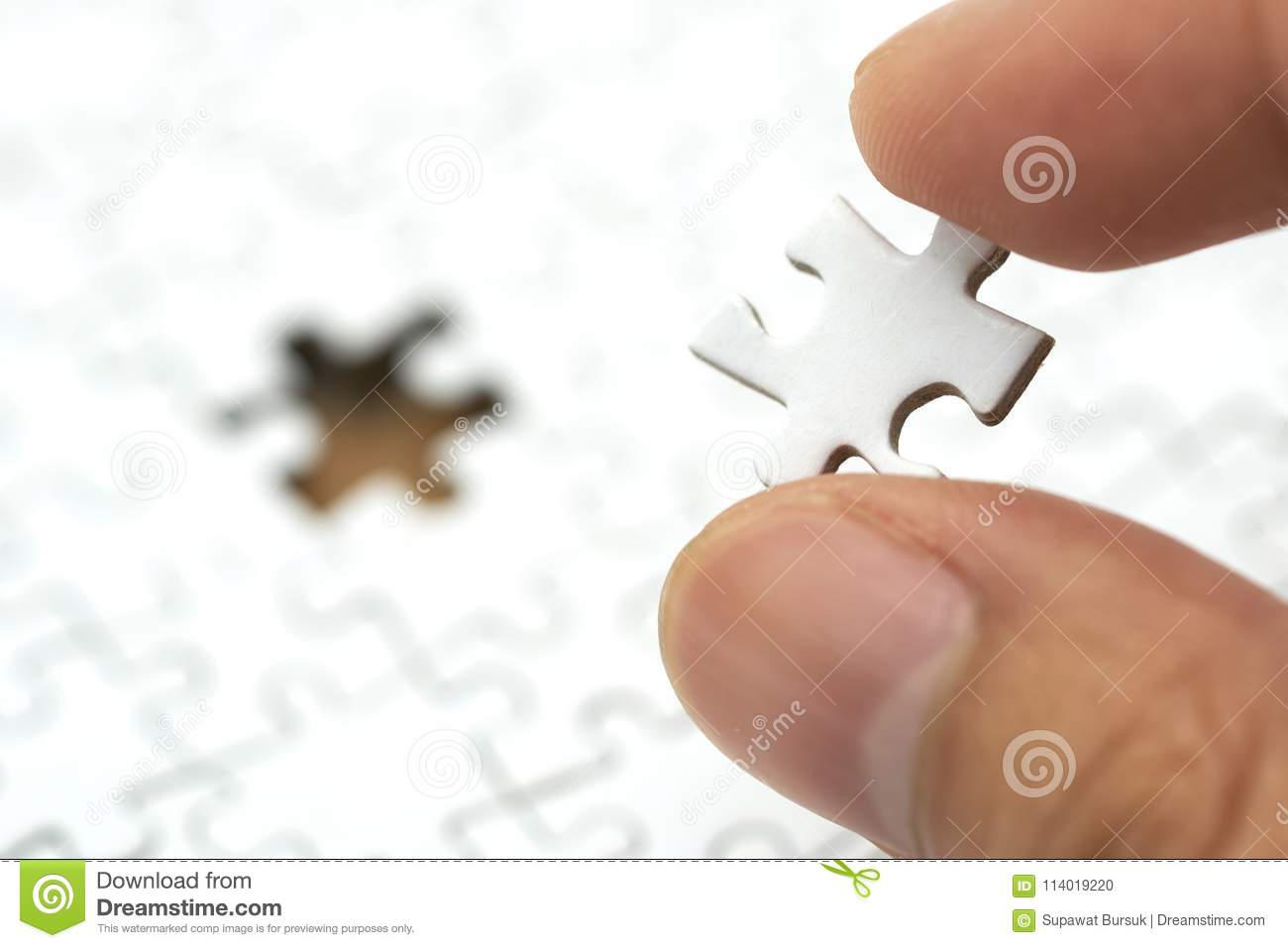 Businessman holding a white Jigsaw is placed on a white Jigsaw.using as background business concept and Strategy concept with copy