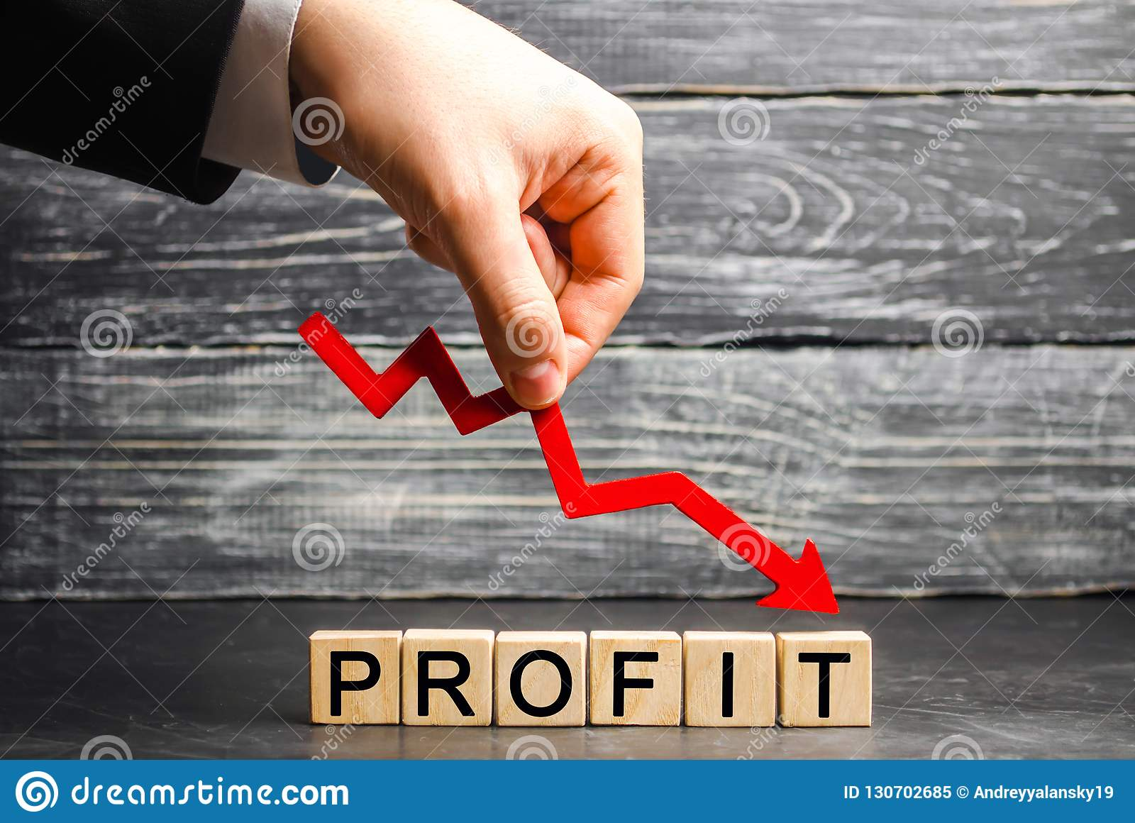 A businessman holds a red arrow to down and the inscription `profit`. Unsuccessful business and poverty. Profit decline. Loss of i