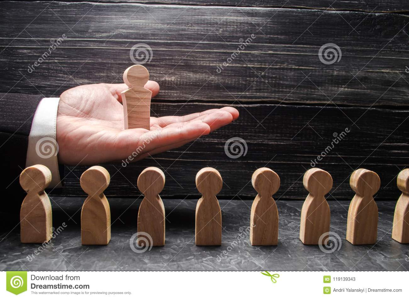 A businessman holds a wooden leader figure on the palm of his hand over a number of other workers. Concept leader, team work.