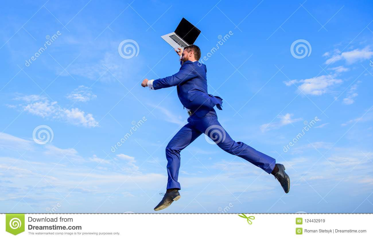 Businessman inspired entrepreneur feels powerful going to change world. Man inspired holds laptop above while jump