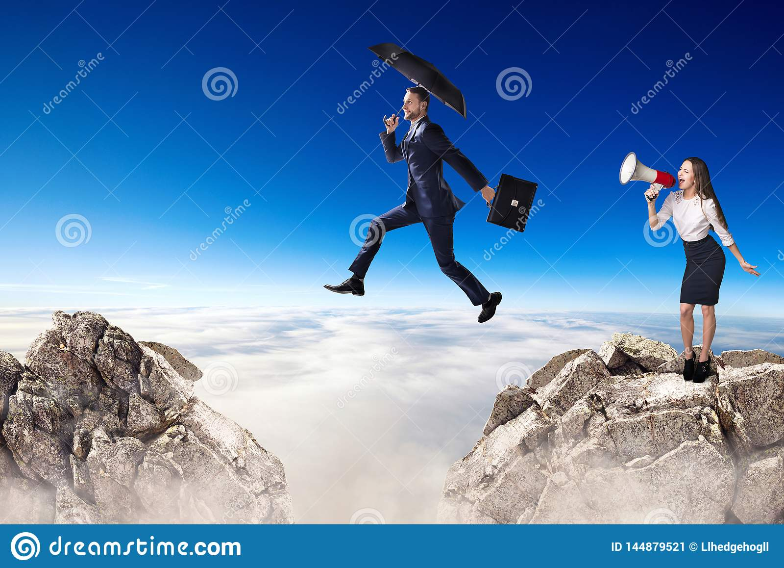 Businessman jumping over a cliff and collegue is cheering with bullhorn.
