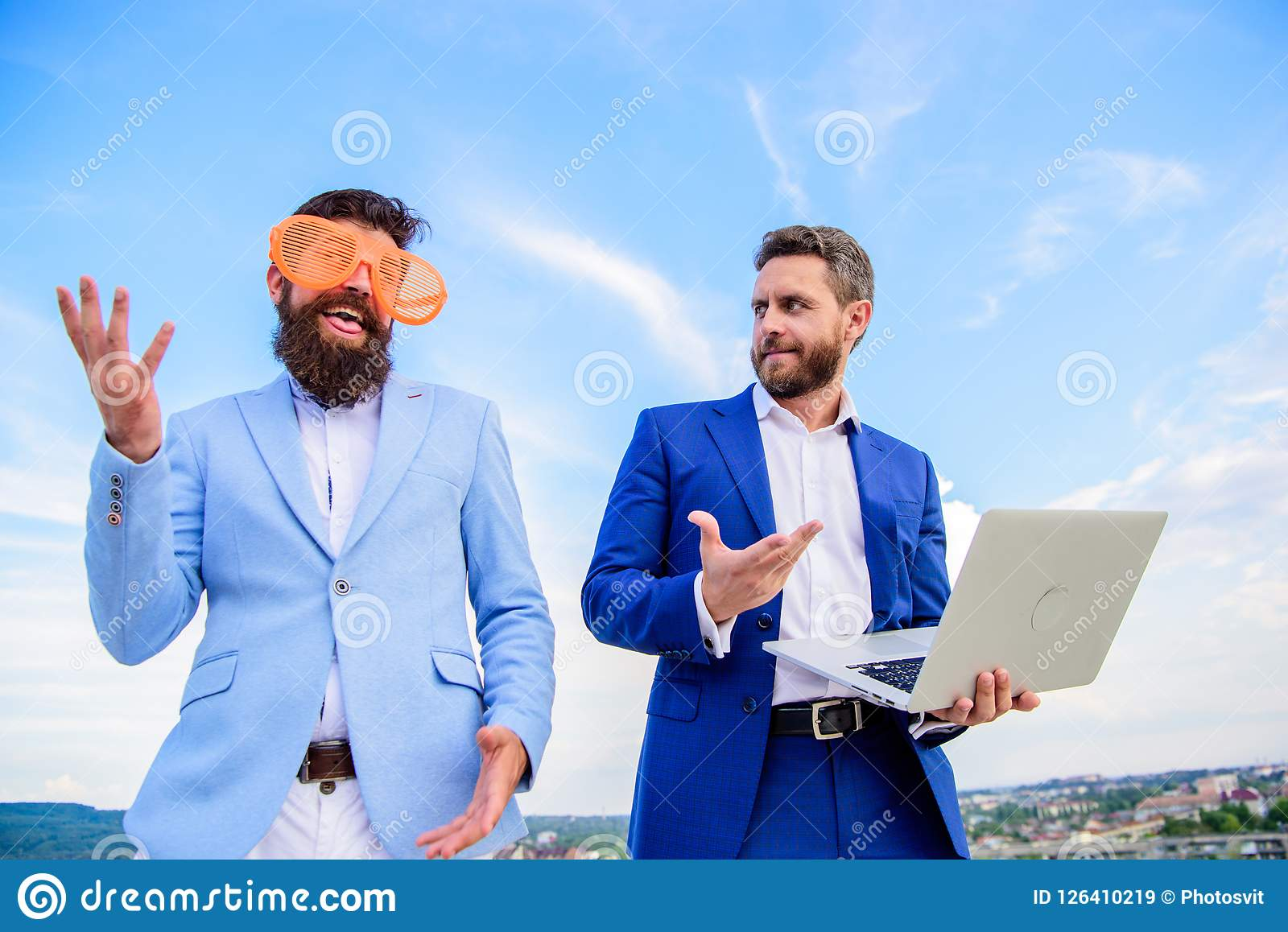 Businessman with laptop serious while business partner ridiculous glasses looks funny. How to stop playing at