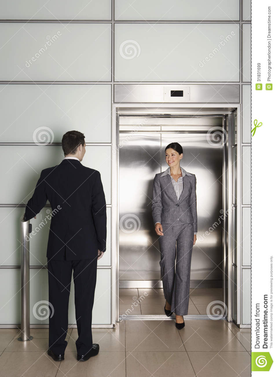 Businessman Looking At Female Colleague Exiting Elevator Royalty ...