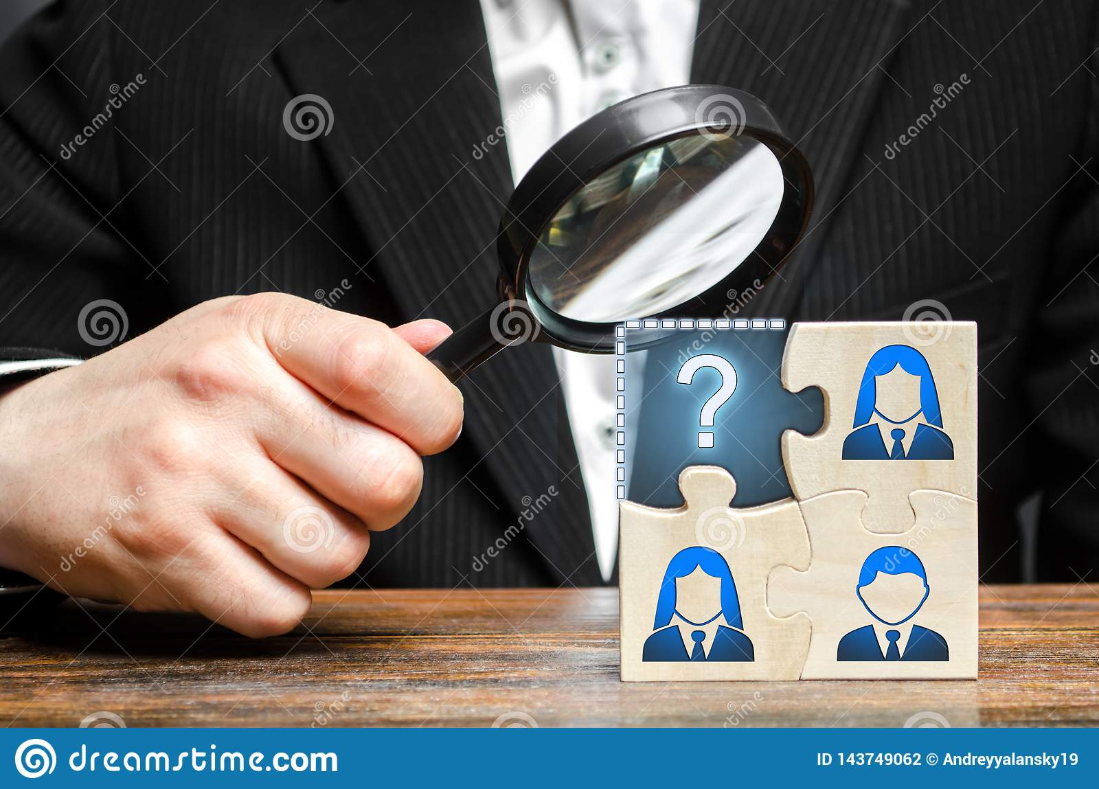 Businessman with a magnifying glass examines the missing part of the puzzle team. Search, recruitment staff, hiring leader