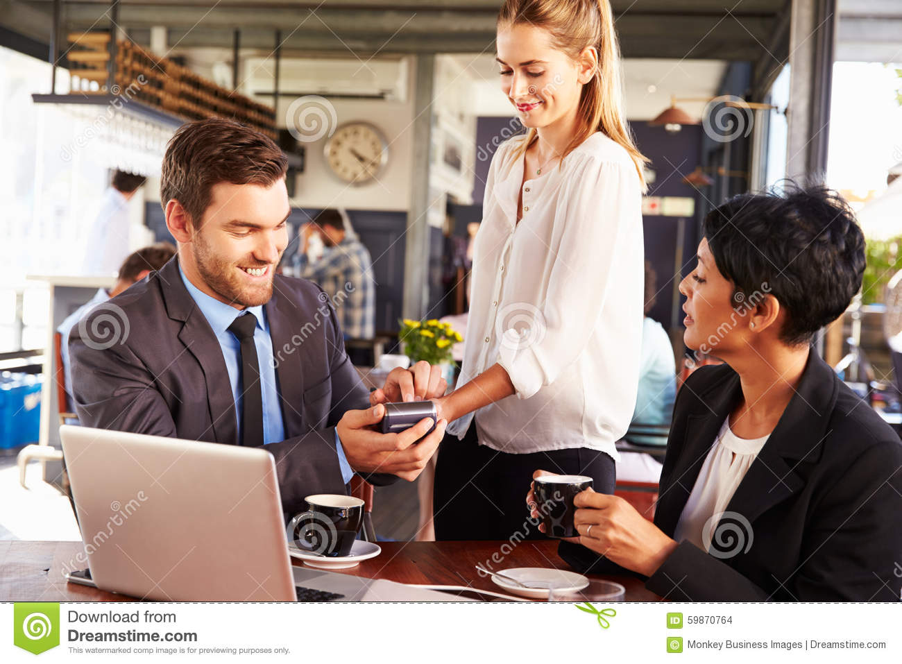 Businessman making credit card payment in a cafe