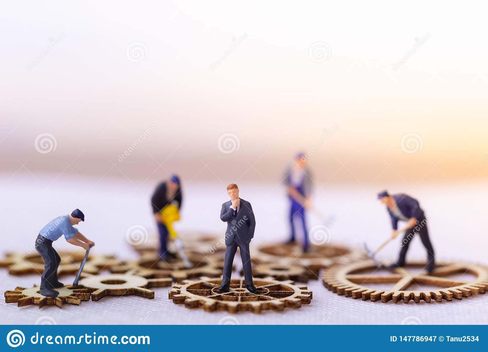 Businessman and many workers standing on wooden gear.