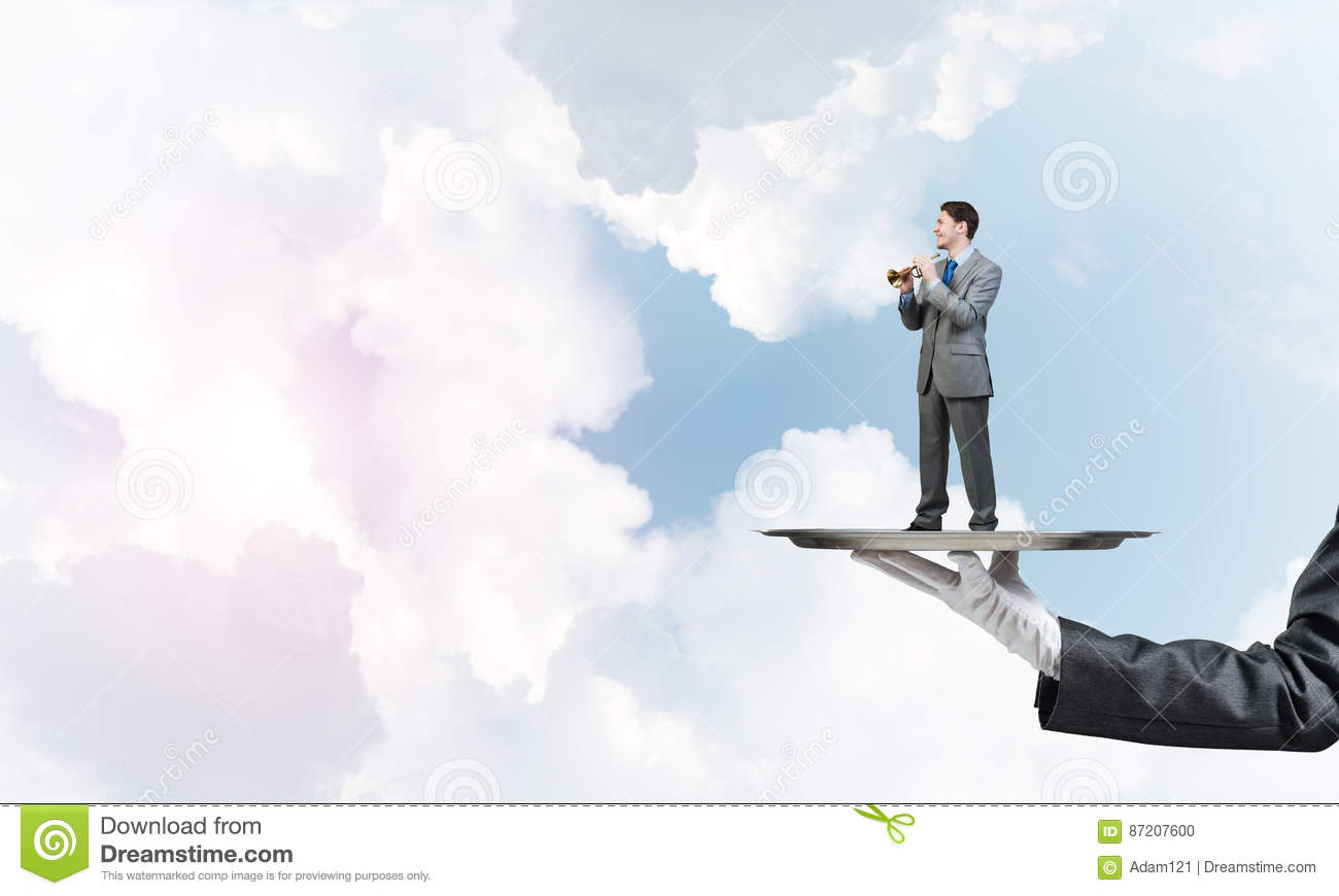 Businessman on metal tray playing fife against blue sky background