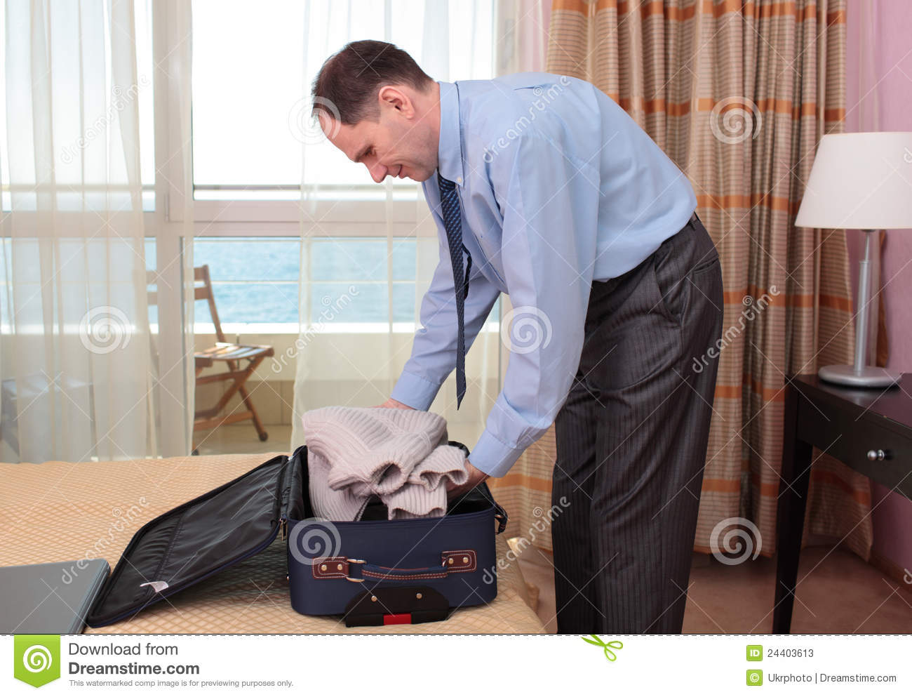 Businessman packing a suitcase